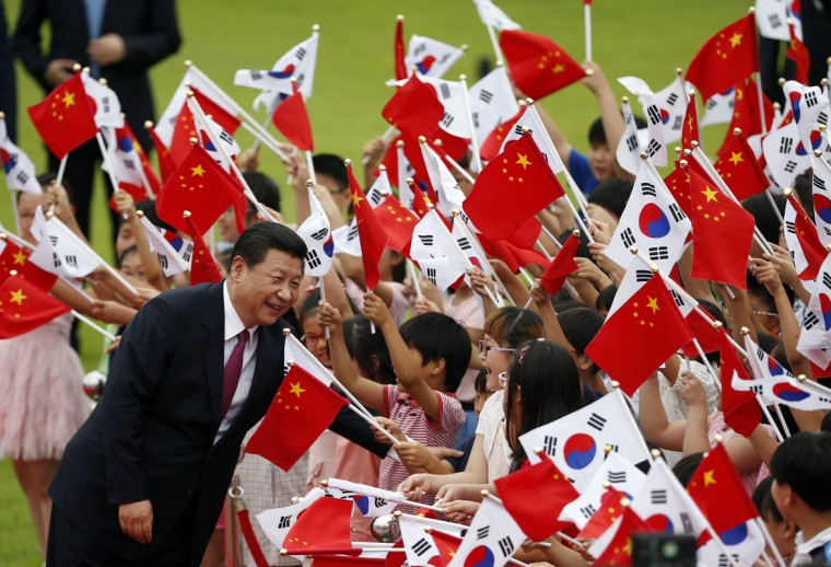 Chinese President Xi Jinping greets children waving Chinese and South Korean national flags during a welcoming ceremony at the presidential Blue House in Seoul July 3, 2014. Xi arrived in South Korea on Thursday, hoping to strengthen commercial and diplomatic ties while Seoul is expected to push Beijing to increase pressure on ally North Korea to end its pursuit of nuclear arms. (Kim Hong-Ji/Reuters)