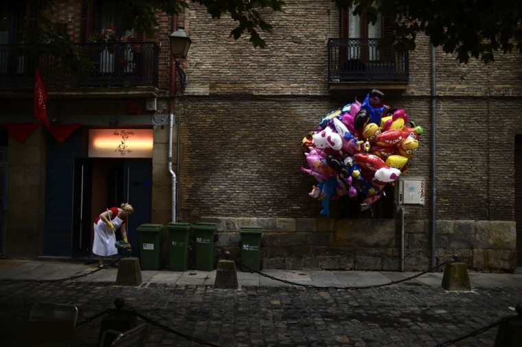 "A woman cleans a bar entrance near a bunch of balloons at the San Fermin festival in Pamplona July 7, 2014. The San Fermin festival, a heady mix of drinking, dancing, late nights and bullfights, made famous by Ernest Hemingway in his novel ""The Sun Also Rises"", runs for nine days until July 14. (REUTERS/Vincent West)"