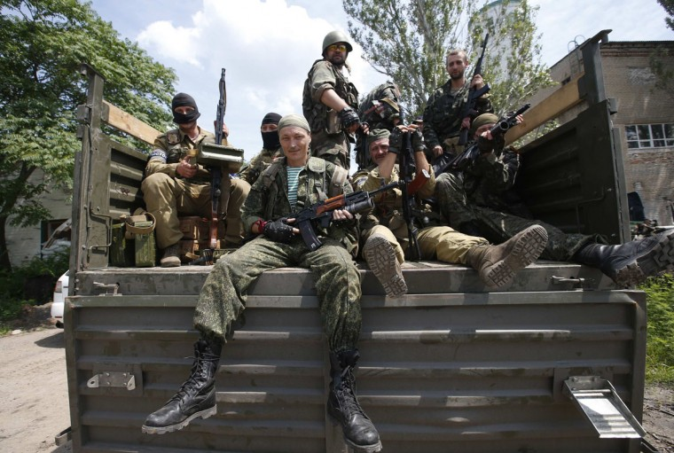 Pro-Russian separatist fighters from the so-called Battalion Vostok (East) sit in a truck as they set out from a base in the eastern Ukrainian city of Donetsk, July 10, 2014. Ukrainian forces regained more ground but sustained further casualties on Thursday in clashes with separatists, while two Western allies urged Russia's Vladimir Putin to exert more pressure on the rebels to find a negotiated end to the conflict. REUTERS/Maxim Zmeyev