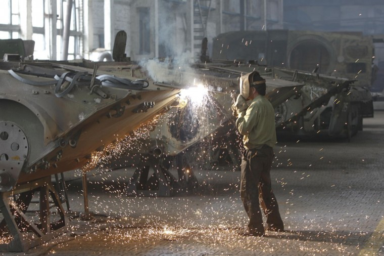 An employee welds while reconditioning an armoured personnel carrier at the 141th Zhytomyr Armor Mechanical Repair Plant in Zhytomyr July 10, 2014. Ukrainian forces regained more ground but sustained further casualties on Thursday in clashes with separatists, while two Western allies urged Russia's Vladimir Putin to exert more pressure on the rebels to find a negotiated end to the conflict. REUTERS/Valentyn Ogirenko