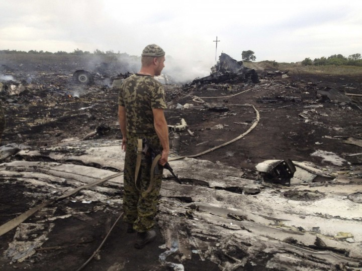 An armed pro-Russian separatist stands at a site of a Malaysia Airlines Boeing 777 plane crash in the settlement of Grabovo in the Donetsk region, July 17, 2014. The Malaysian airliner MH-17 was shot down over eastern Ukraine by pro-Russian militants on Thursday, killing all 295 people aboard, a Ukrainian interior ministry official said. Dozens of bodies were scattered around the smoldering wreckage of a passenger jet that crashed in a field in eastern Ukraine on Thursday, a Reuters reporter said. An emergency services rescue worker said at least 100 bodies had so far been found at the scene, near the village of Grabovo, and that debris from the wreckage was spread across an area up to about 15 km (nine miles) in diameter. (Maxim Zmeyev/Reuters)