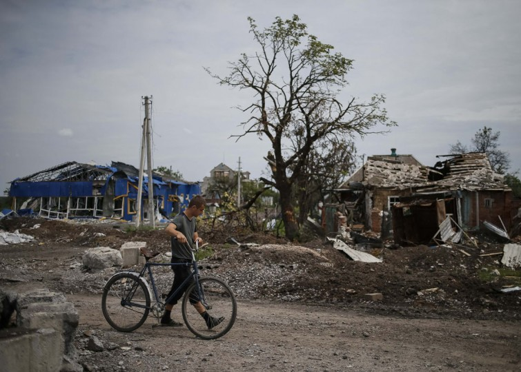 A local resident pushes his bicycle past buildings damaged by a recent shelling in the eastern Ukrainian village of Semenovka July 9, 2014. Ukraine said on Wednesday it was confident of receiving further aid under a $17 billion IMF bailout but appealed to Western institutions and donors for further cash and credit to rebuild the east, shattered by separatist conflict. REUTERS/Gleb Garanich