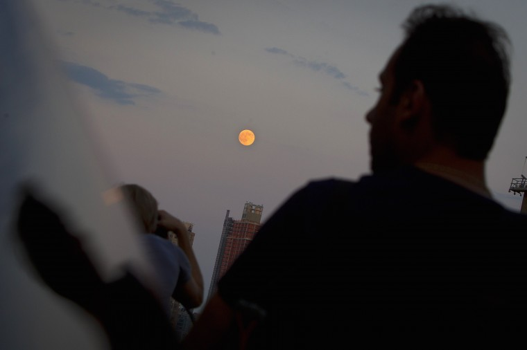 A man is reflected in a car window as he looks at the moon one day ahead of the Supermoon phenomenon from a bridge over 42nd St. in the Manhattan borough of New York July 11, 2014. Occurring when a full moon or new moon coincides with the closest approach the moon makes to the Earth, the Supermoon results in a larger-than-usual appearance of the lunar disk. REUTERS/Carlo Allegri