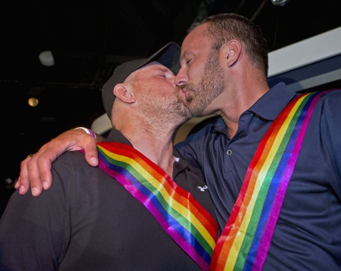 William Lee Jones (L) and Aaron Huntsman kiss during a celebration in Key West, Forida in this handout photo provided by the Florida Keys News Bureau July 17, 2014. Jones, Huntsman and about 100 other people marked a  Florida Keys judge's ruling overturning Florida's ban on same-sex marriage on Thursday after the couple's legal challenge, the latest in a string of court rulings across the United States voiding the state laws that restrict the right of same-sex couples to marry.    || PHOTO CREDIT: ANDY NEWMAN/FLORIDA KEYS NEWS BUREAU/HANDOUT VIA REUTERS    - REUTERS