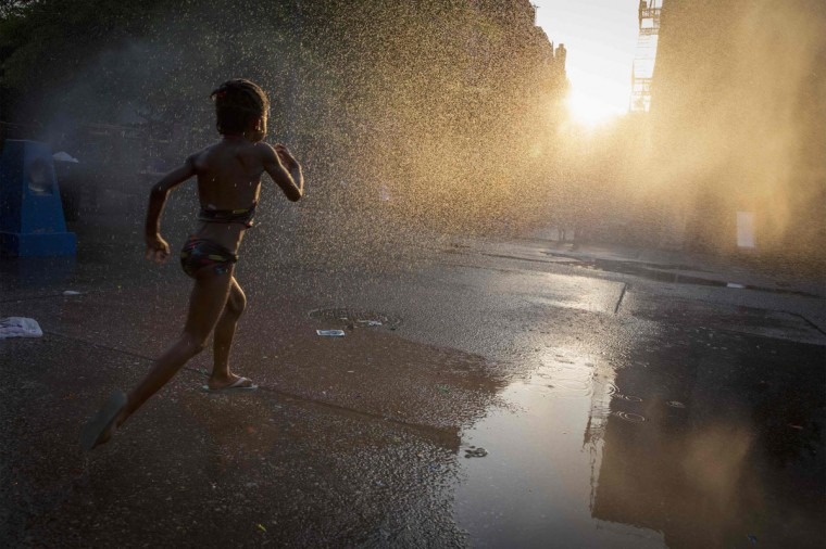 A young girl runs through a sprinkler at a playground in the Brooklyn borough of New York July 7, 2014. (REUTERS/Brendan McDermid)
