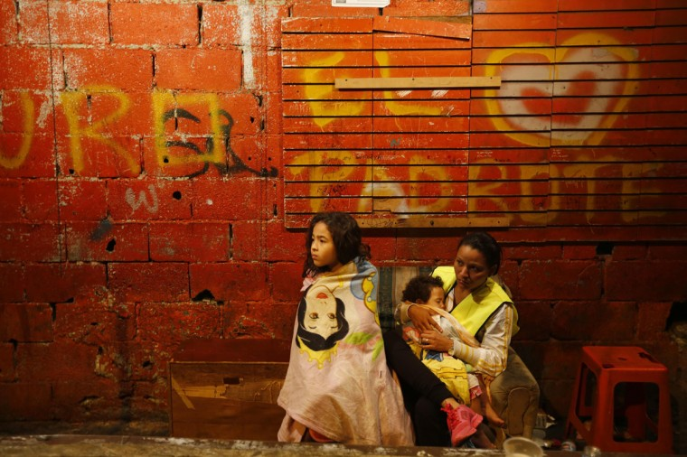 "Evicted residents of Tower of David wait for a bus to transport them to their new house in Caracas July 22, 2014. Venezuelan soldiers and officials began moving hundreds of families on Tuesday out of a half-built 45-story skyscraper that dominates the Caracas skyline and is thought to be the tallest slum in the world. The mass eviction from the ""Tower of David"", originally intended to be a bank center but abandoned since 1994 and later home to some 3,000 needy Venezuelans, proceeded peacefully. (Jorge Silva/Reuters)"