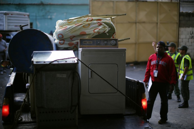 "Belongings of an evicted resident of the ""Tower of David"" are seen as national guards transport them to a new house, in Caracas July 22, 2014. Venezuelan soldiers and officials began moving hundreds of families on Tuesday out of a half-built 45-story skyscraper that dominates the Caracas skyline and is thought to be the world's tallest slum. The mass eviction from the ""Tower of David"", originally intended to be a bank center but abandoned since 1994 and later home to some 3,000 needy Venezuelans, proceeded peacefully. (Jorge Silva/Reuters)"