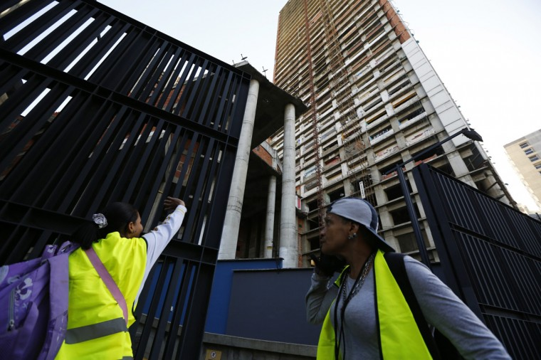 "Evicted residents of Tower of David walk out the building to a bus which will transport them to their new house in Caracas July 22, 2014. Venezuelan soldiers and officials began moving hundreds of families on Tuesday out of a half-built 45-story skyscraper that dominates the Caracas skyline and is thought to be the tallest slum in the world. The mass eviction from the ""Tower of David"", originally intended to be a bank center but abandoned since 1994 and later home to some 3,000 needy Venezuelans, proceeded peacefully. (Jorge Silva/Reuters)"
