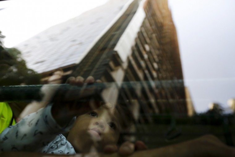 "An evicted resident of Tower of David sits in a bus, as the building is reflected on the window, which will transport them to the new home in Caracas July 22, 2014. Venezuelan soldiers and officials began moving hundreds of families on Tuesday out of a half-built 45-story skyscraper that dominates the Caracas skyline and is thought to be the tallest slum in the world. The mass eviction from the ""Tower of David"", originally intended to be a bank center but abandoned since 1994 and later home to some 3,000 needy Venezuelans, proceeded peacefully. (Jorge Silva/Reuters)"