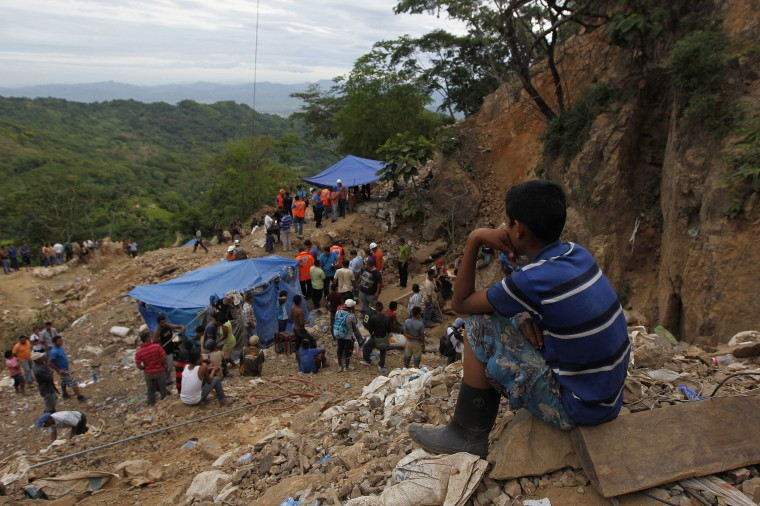 A child sits as he looks at miners and rescue workers the site of a landslide at a gold mine in San Juan Arriba, on the outskirts of Tegucigalpa. (REUTERS/Jorge Cabrera)