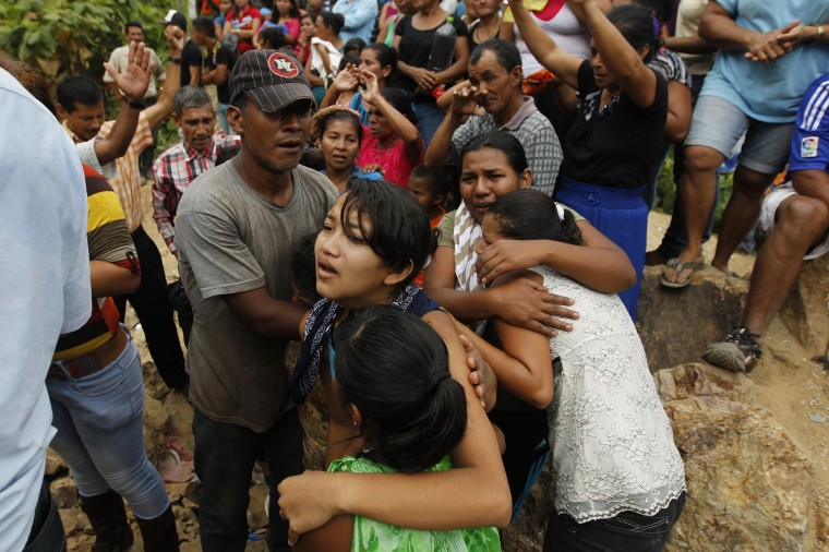 Relatives of trapped miners react as people pray at the site of a landslide at a gold mine in San Juan Arriba, on the outskirts of Tegucigalpa. (REUTERS/Jorge Cabrera)