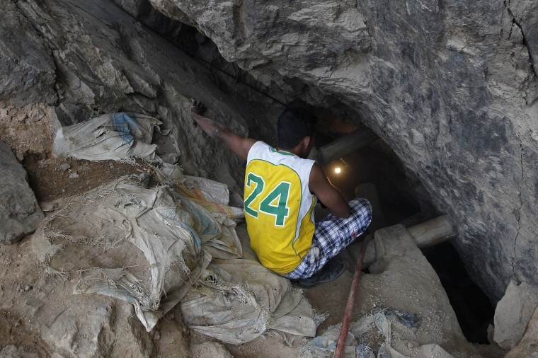 A miner holds a torch to illuminate the area through a crack on the floor at the site of a landslide at a gold mine in San Juan Arriba, on the outskirts of Tegucigalpa. (REUTERS/Jorge Cabrera)