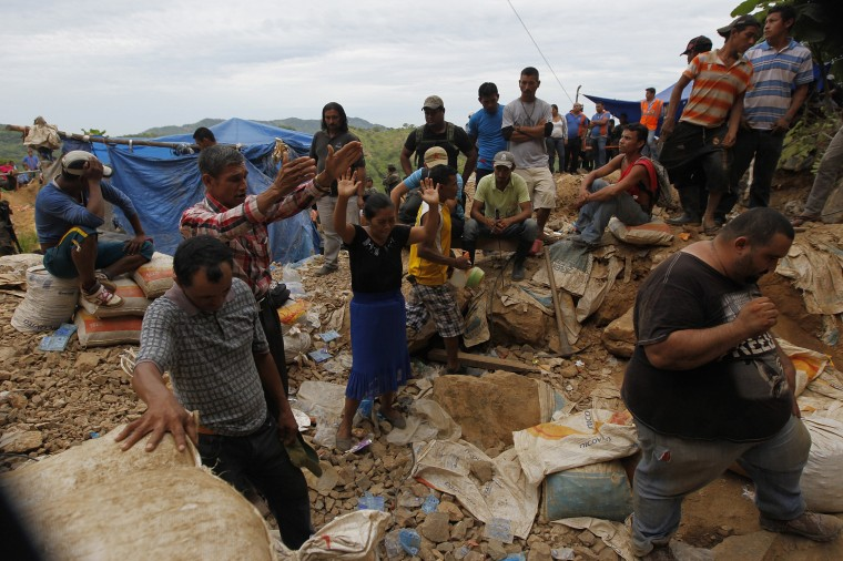 Residents pray at the site of a landslide at a gold mine in San Juan Arriba, on the outskirts of Tegucigalpa. (REUTERS/Jorge Cabrera)