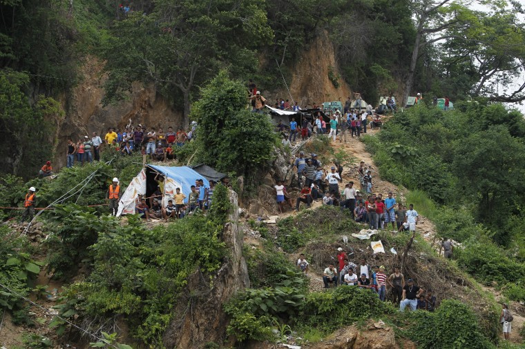Miners and rescue workers stand at the site of a landslide at a gold mine in San Juan Arriba, on the outskirts of Tegucigalpa. (REUTERS/Jorge Cabrera)