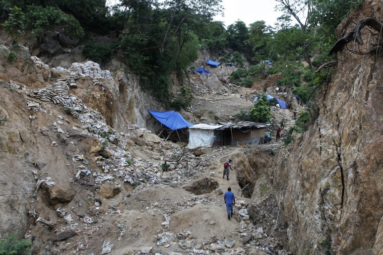 Miners walk pass maakeshift tents near the site of a landslide at a gold mine in San Juan Arriba, on the outskirts of Tegucigalpa. (REUTERS/Jorge Cabrera)