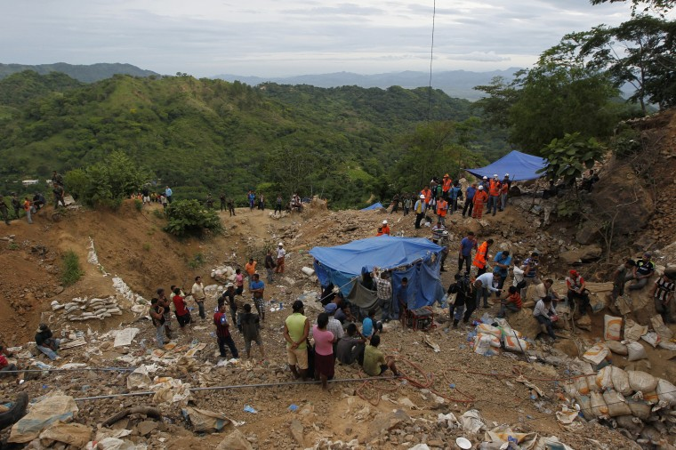 Residents and rescue workers stand at the site of a landslide at a gold mine in San Juan Arriba, on the outskirts of Tegucigalpa. (REUTERS/Jorge Cabrera)
