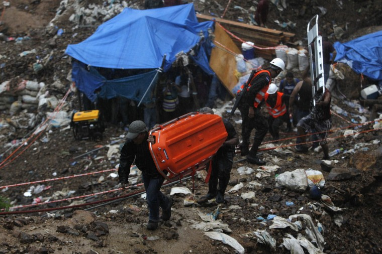 Miners carry stretchers as other take cover from rain in a makeshift tent at the site of a landslide at a gold mine in San Juan Arriba, outskirts of Tegucigalpa. (REUTERS/Jorge Cabrera)