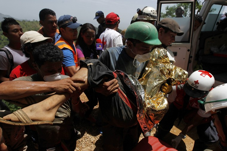 A miner carries a colleague to an ambulance after being rescued from a gold mine blocked by a landslide in San Juan Arriba, outskirts of Tegucigalpa. (REUTERS/Jorge Cabrera)