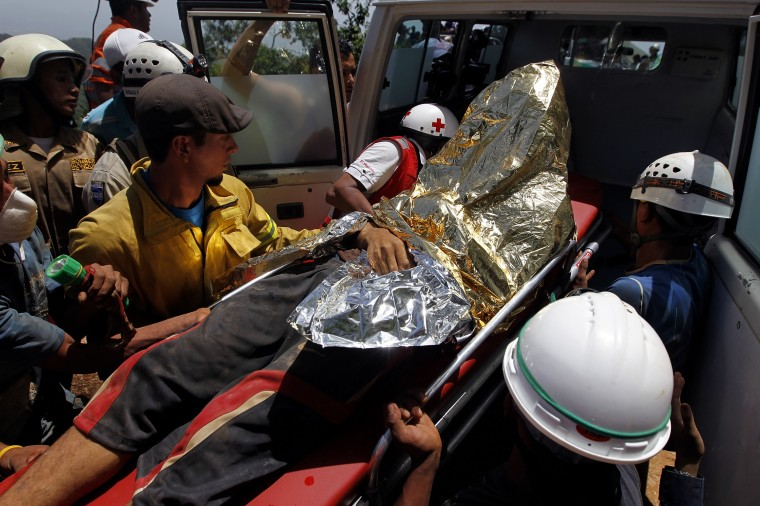 A miner rescued from a gold mine blocked by a landslide is carried into an ambulance in San Juan Arriba, outskirts of Tegucigalpa. (REUTERS/Jorge Cabrera)