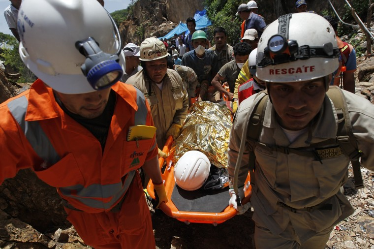 Rescue workers carry a miner, wrapped in a survival blanket, after being rescued from a gold mine blocked by a landslide in San Juan Arriba, outskirts of Tegucigalpa. (REUTERS/Jorge Cabrera)