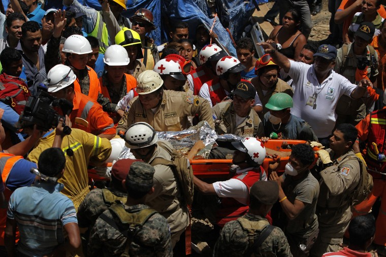 A miner is carried by paramedics after being rescued from a gold mine blocked by a landslide in San Juan Arriba, outskirts of Tegucigalpa. (REUTERS/Jorge Cabrera)