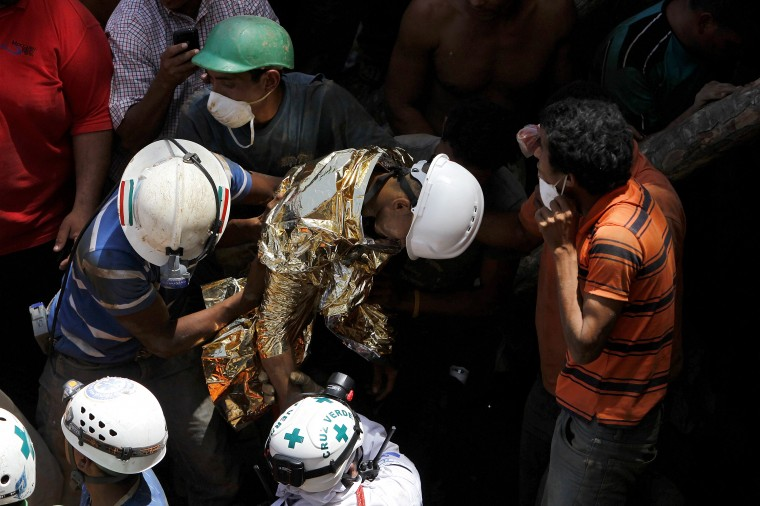 Miners and rescue workers hold a miner, wrapped in a survival blanket, rescued from a gold mine blocked by a landslide in San Juan Arriba, outskirts of Tegucigalpa. (REUTERS/Jorge Cabrera)