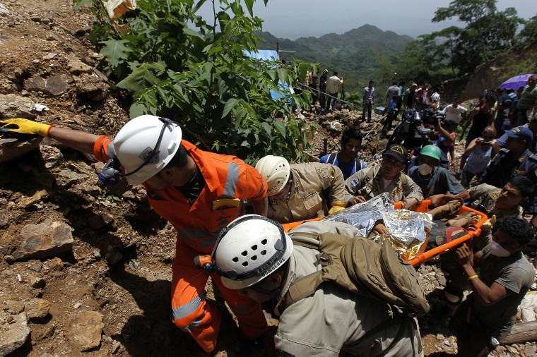 Firefighters and rescue workers carry stretchers with miners rescued from a gold mine blocked by a landslide in San Juan Arriba, outskirts of Tegucigalpa. (REUTERS/Jorge Cabrera)