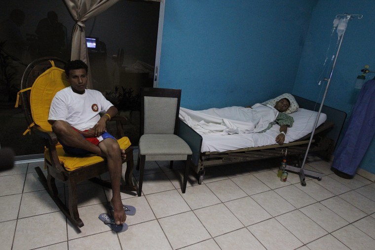 A miner, rescued from a gold mine affected by a landslide, lies in bed as a relative sits next to him at a hospital in Choluteca, on the outskirts of Tegucigalpa. (REUTERS/Jorge Cabrera)