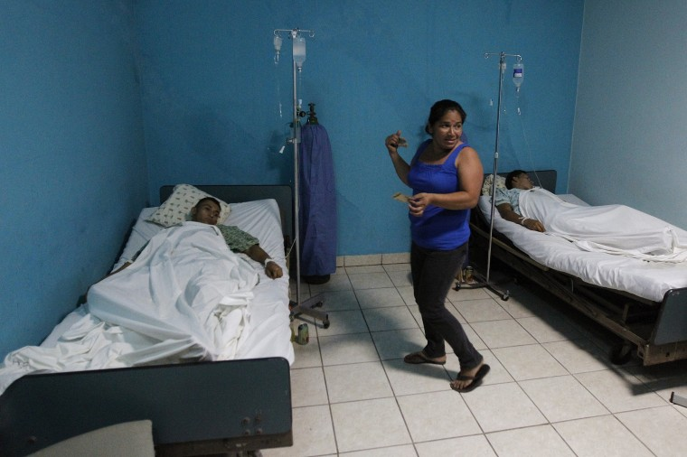 Miners, rescued from a gold mine affected by a landslide, lie in beds as a relative stands next to them at a hospital in Choluteca, on the outskirts of Tegucigalpa. (REUTERS/Jorge Cabrera)