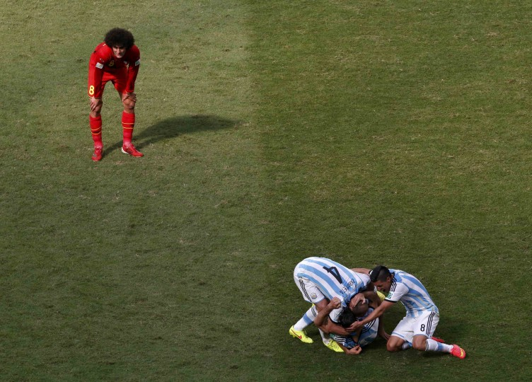 Argentina's players celebrate past Belgium's Marouane Fellaini (left) after winning their 2014 World Cup quarterfinal match. (REUTERS/David Gray)