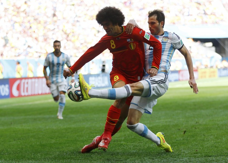 Belgium's Marouane Fellaini (front) fights for the ball with Argentina's Jose Basanta during their 2014 World Cup quarterfinal match. (REUTERS/Dominic Ebenbichler)
