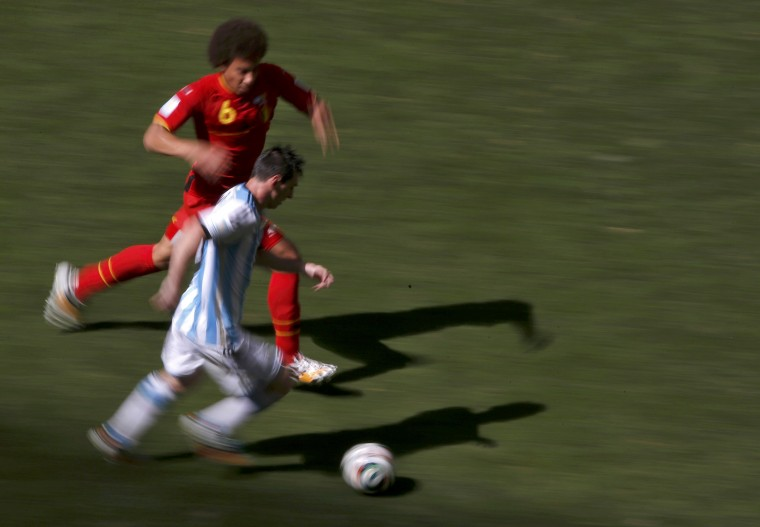 Argentina's Lionel Messi (right) chases the ball with Belgium's Axel Witsel. (REUTERS/David Gray)