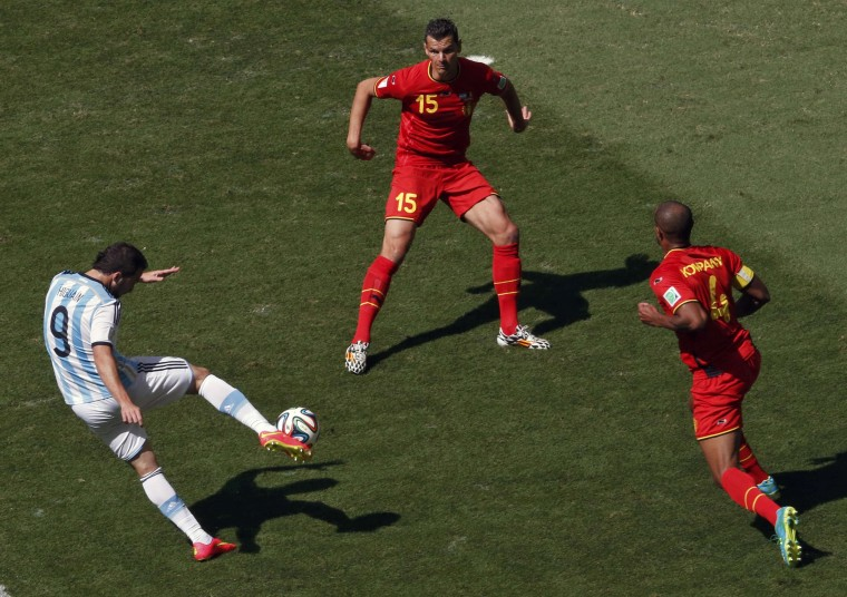 Argentina's Gonzalo Higuain (left) kicks the ball to score a goal past Belgium's Daniel Van Buyten (center) and Vincent Kompany. (REUTERS/David Gray)