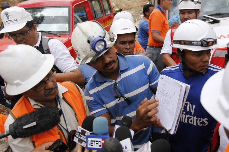 Engineer Esteban Estrada (center) explains to journalists a plan to reach the area of a gold mine affected by a landslide, where eight miners remain trapped in San Juan Arriba, on the outskirts of Tegucigalpa. (REUTERS/Jorge Cabrera)
