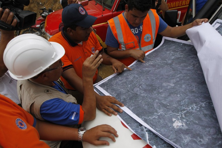 Civil Protection personnel check maps to plan a rescue operation for eight miners who remain trapped at a gold mine affected by a landslide in San Juan Arriba, on the outskirts of Tegucigalpa. (REUTERS/Jorge Cabrera)