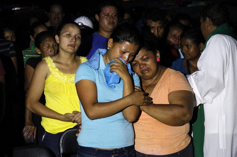 The relatives of a miner trapped in a gold mine affected by a landslide react during a mass in San Juan Arriba, outskirts of Tegucigalpa. (REUTERS/Jorge Cabrera)
