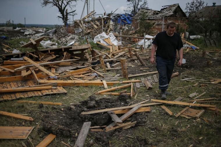 A local resident walks past buildings damaged by a recent shelling in the eastern Ukrainian village of Semenovka on July 9, 2014. (REUTERS/Gleb Garanich)