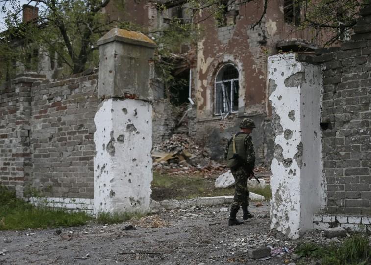 A Ukrainian serviceman inspects a building damaged by a recent shelling in the eastern Ukrainian village of Semenovka on July 9, 2014. (REUTERS/Gleb Garanich)