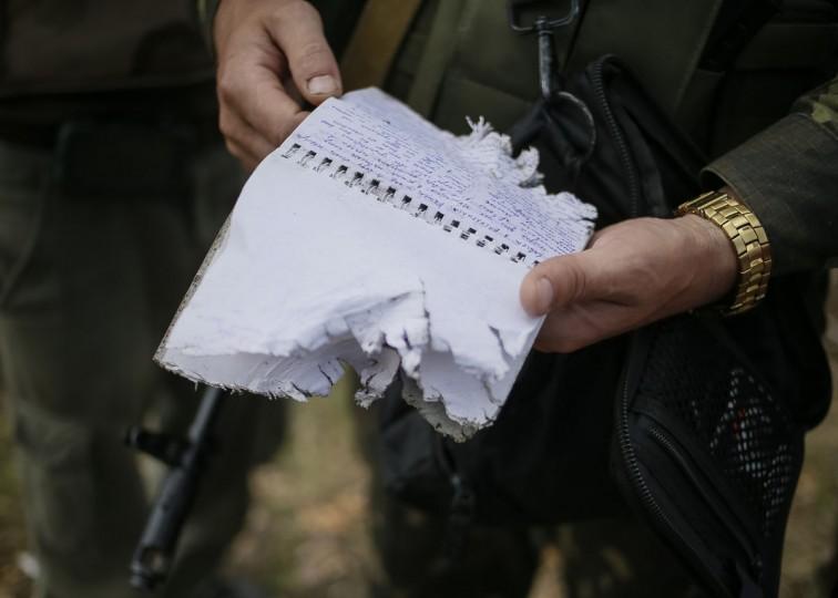 A Ukrainian serviceman reads letters by a pro-Russian separatist found near a destroyed separatist position in the eastern Ukrainian village of Semenovka on July 9, 2014. (REUTERS/Gleb Garanich)