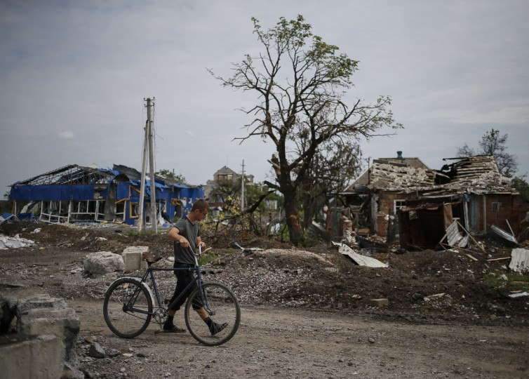 A local resident pushes his bicycle past buildings damaged by a recent shelling in the eastern Ukrainian village of Semenovka on July 9, 2014. (REUTERS/Gleb Garanich)