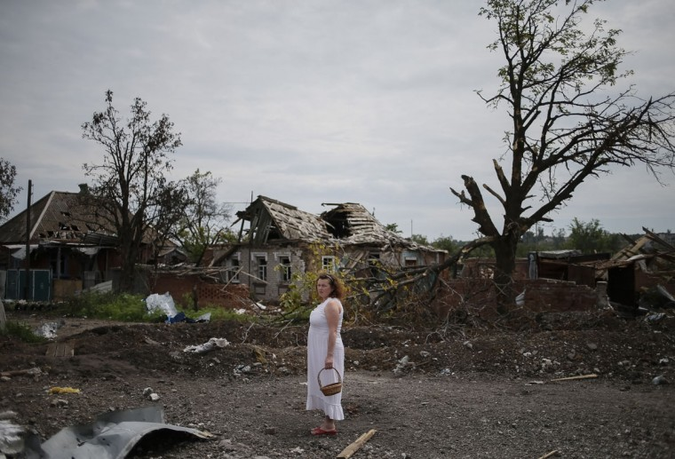 A local resident stands outside buildings damaged by a recent shelling in the eastern Ukrainian village of Semenovka on July 9, 2014. (REUTERS/Gleb Garanich)