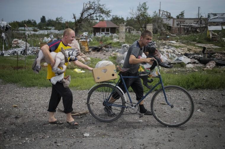 Local residents walk past buildings damaged by a recent shelling in the eastern Ukrainian village of Semenovka on July 9, 2014. (REUTERS/Gleb Garanich)
