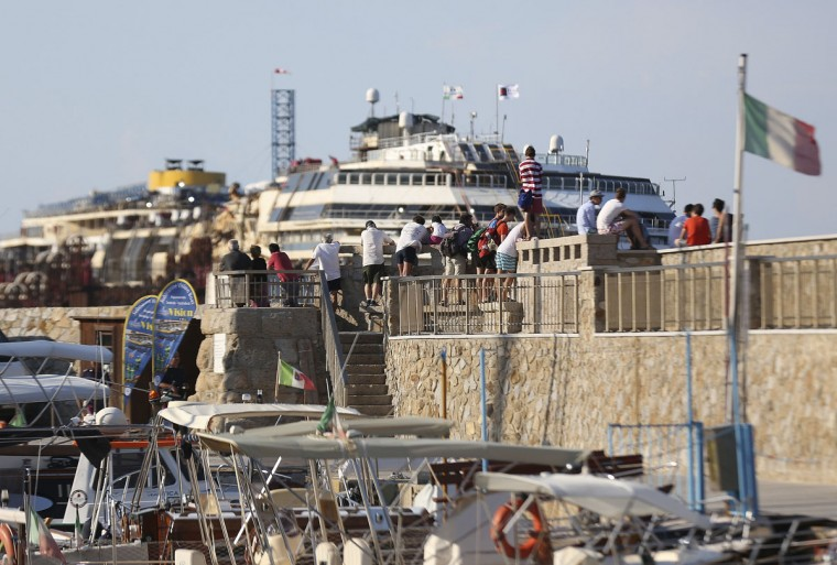 People look the cruise liner Costa Concordia at Giglio harbor at Giglio Island July 16, 2014. (REUTERS/Alessandro Bianchi)