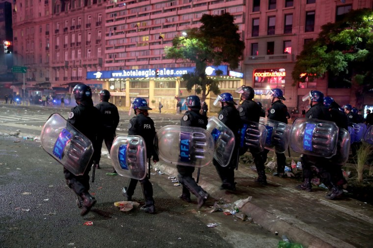 Police officers wearing riot gear control Argentina soccer fans that became violent near the Obelisco de Buenos Aires after their team lost to Germany 1-0 during the World Cup final. (Photo by Joe Raedle/Getty Images)