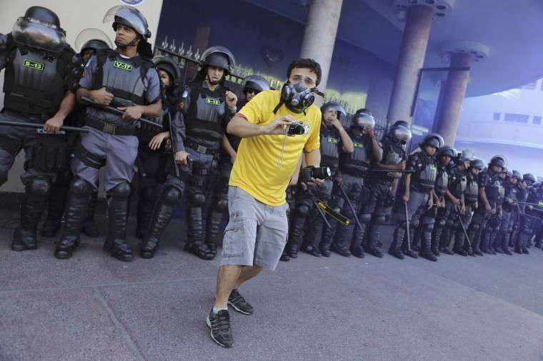 A demonstrator wearing a Brazil jersey films with his cameras in front of riot police during clashes before the World Cup final match between Argentina and Germany in Rio de Janeiro. (REUTERS/Nacho Doce)