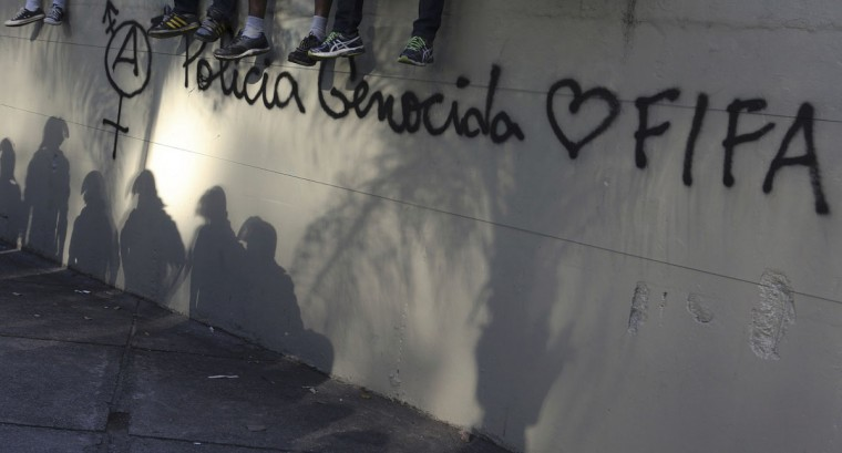 "The shadows of riot police are seen on a wall during a protest before the World Cup final match between Argentina and Germany in Rio de Janeiro. The phrase written on the wall reads ""The police are genocides."" (REUTERS/Nacho Doce)"