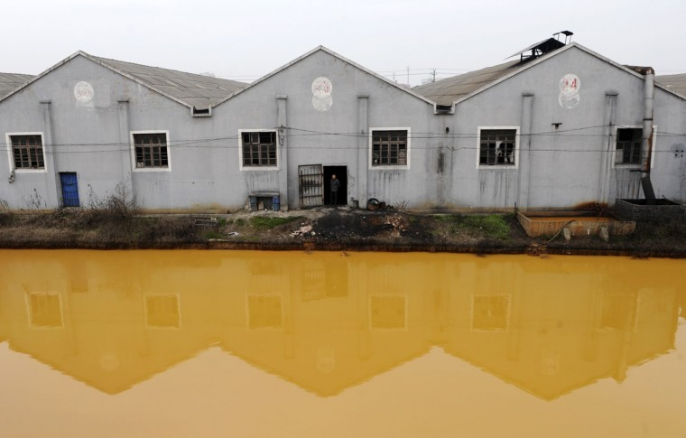 A worker looks at a photographer from a door of a factory manufacturing screws and nuts next to a polluted river in Jiaxing, Zhejiang province March 15, 2012. (REUTERS/Stringer)