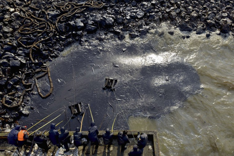 Workers clean up leaked oil after an oil pipeline explosion last week in Qingdao, Shandong province November 25, 2013. (REUTERS/Stringer)