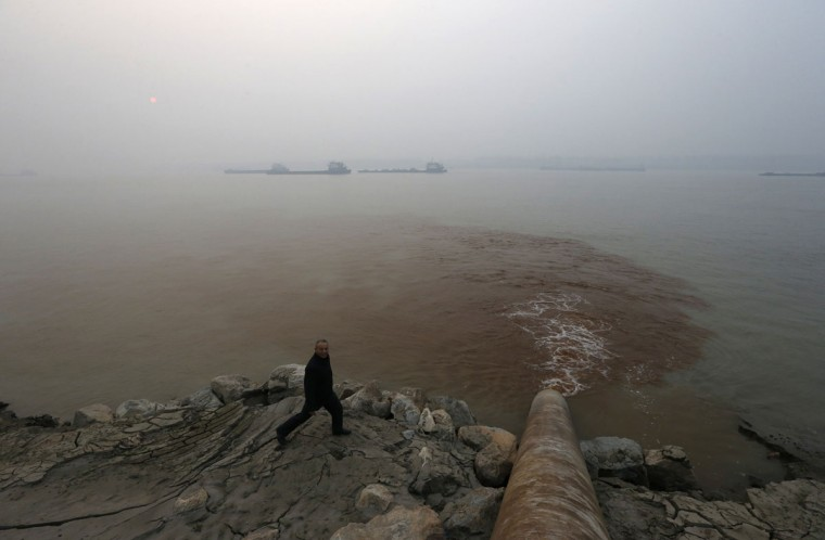 A man walks by a pipe discharging waste water into the Yangtze River from a paper mill in Anqing, Anhui province, December 4, 2013. (REUTERS/William Hong)