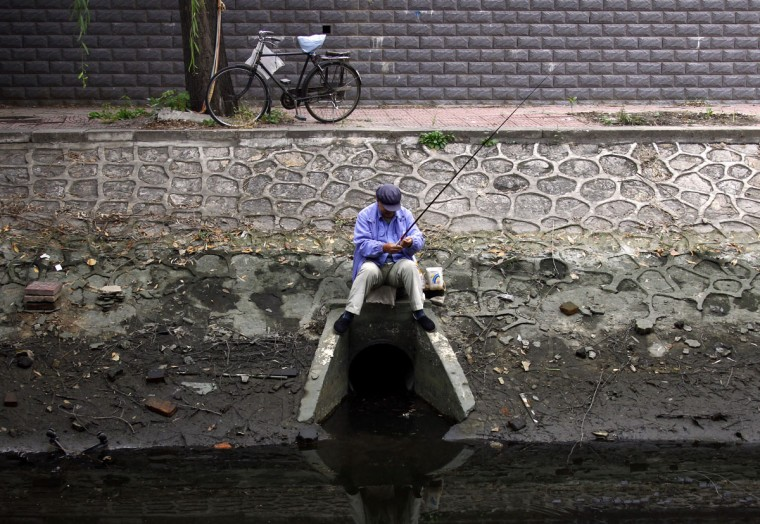 A man sits atop a drain as he fishes at a polluted canal in central Beijing on October 26, 2010. (REUTERS/David Gray)